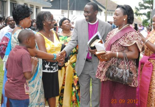 14 Bishop & wife greetig R. Kavuma. GOGA chair looks on